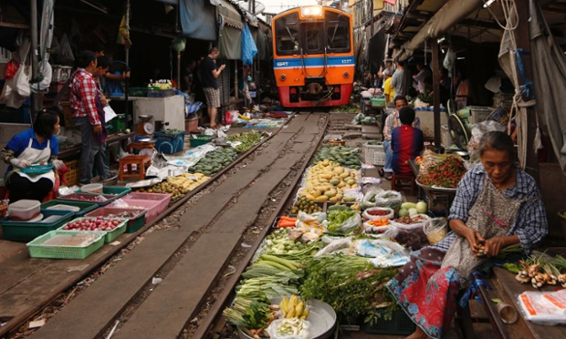 Rom Hoop market or Folding Umbrella Market where vendors and shoppers dodge bustling while commuter train pass through eight times a day